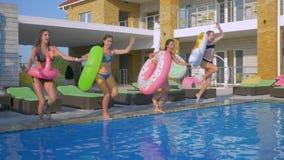 De jonge aantrekkelijke vrouwenvrienden in zwempakken met opblaasbare ringen springen in blauw water van zwembad terwijl het onts stock footage