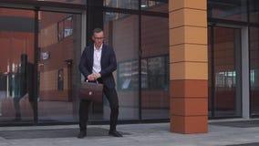 De jonge aantrekkelijke Zakenman in glazen danst dichtbij het commerciële centrum die een aktentas in zijn handen houden HD stock video