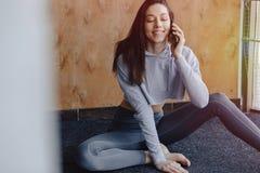 De jonge aantrekkelijke zitting van het geschiktheidsmeisje op de vloer dichtbij het venster op de achtergrond die van een houten royalty-vrije stock afbeelding