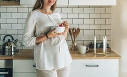 De jonge aantrekkelijke zwangere vrouw bevindt zich in keuken, die op lijst leunen, houdend kom in haar handen De mens bevindt zi Stock Foto's