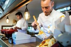 De jonge aardappels van de chef-kok dienende barbecue in een voedselvrachtwagen stock afbeeldingen