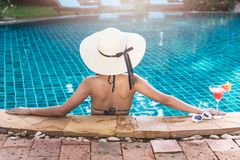 De jonge achtervrouw in het zwembad van de bikiniluxe drinkt cocktail royalty-vrije stock foto