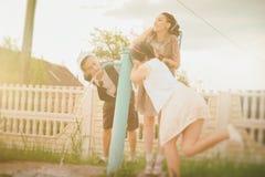 De jonge actieve meisjes en kerelhipsters hebben de waterzomer drinken Stock Afbeeldingen