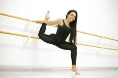 De jonge actieve vrouw in een t-shirt en beenkappen, voert het uitrekken zich en yogaoefeningen in een moderne studio uit stock foto's