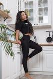 De jonge actieve vrouw in een t-shirt en beenkappen, voert het uitrekken zich en yogaoefeningen in een moderne studio uit royalty-vrije stock fotografie