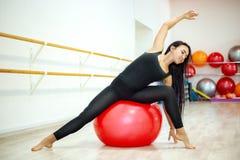 De jonge actieve vrouw in een t-shirt en beenkappen, voert het uitrekken zich en yogaoefeningen in een moderne studio uit royalty-vrije stock foto's