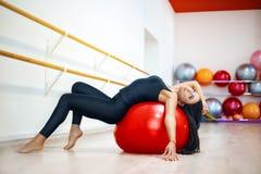 De jonge actieve vrouw in een t-shirt en beenkappen, voert het uitrekken zich en yogaoefeningen in een moderne studio uit stock foto