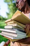 De jonge Afrikaanse Amerikaanse stapel van de mensenholding van boeken in park Stock Foto's