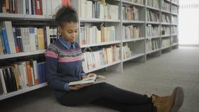 De jonge Afrikaanse Amerikaanse vrouw leest boekzitting op vloer in universitaire bibliotheek stock video