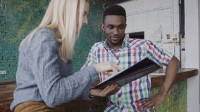 De jonge Afrikaanse man en de Kaukasische vrouw zitten dichtbij de barteller op modern kantoor en het bespreken van de documenten Stock Afbeeldingen