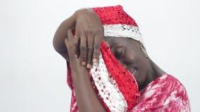 De jonge Afrikaanse vrouw bindt haar hoofd met een sjaal stock videobeelden