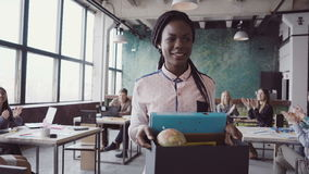 De jonge Afrikaanse vrouw die onlangs voor collectieve baan wordt ingehuurd komt in nieuw bureau Het wijfje houdt doos met persoo royalty-vrije stock fotografie