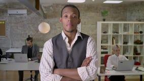De jonge Afrikaanse zakenman bevindt zich met gekruiste wapens en let op bij camera in bureau, het denken concept, collega's stock videobeelden