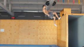 De jonge ambitieuze atleet doet oefening op de lucht na het duwen van de houten raad stock videobeelden