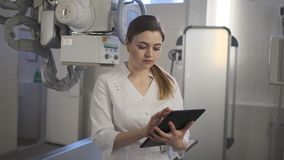 De jonge arts controleert de diagnose op de tablet R?ntgenstraalmachine stock footage