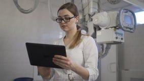 De jonge arts controleert de diagnose op de tablet R?ntgenstraalmachine stock videobeelden