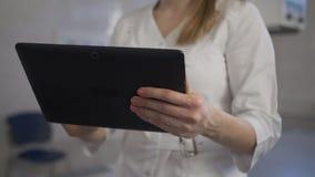 De jonge arts controleert de diagnose op de tablet R?ntgenstraalmachine Sluit omhoog stock video
