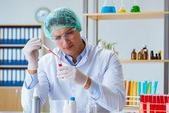 De jonge arts die aan bloedonderzoek in het laboratoriumziekenhuis werken Royalty-vrije Stock Foto