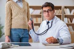 De jonge arts die patiënt met stethoscoop onderzoeken Stock Foto's