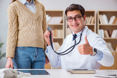 De jonge arts die patiënt met stethoscoop onderzoeken Royalty-vrije Stock Afbeelding