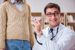 De jonge arts die patiënt met stethoscoop onderzoeken Royalty-vrije Stock Foto's