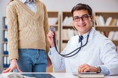 De jonge arts die patiënt met stethoscoop onderzoeken Royalty-vrije Stock Foto