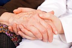 De jonge arts houdt de bejaardehanden royalty-vrije stock foto