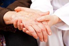 De jonge arts houdt de bejaardehanden royalty-vrije stock foto's