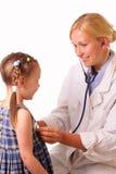De jonge artsenvrouw onderzoekt een kind Royalty-vrije Stock Fotografie