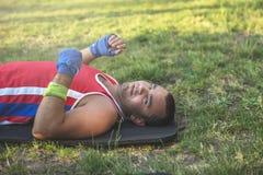 De jonge atleet ligt op zijn rug op het gras tijdens een pauze op a royalty-vrije stock foto