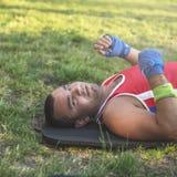 De jonge atleet ligt op zijn rug op het gras tijdens een pauze op a royalty-vrije stock foto's