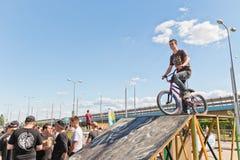De jonge atleet op BMX-fiets is op de helling bereid te springen Stock Foto