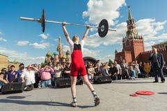 De jonge atleet in rood heft barbell op Stock Afbeelding