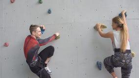 De jonge atleten schikten een gelijke bij de het beklimmen muur Meisje en jongen in alpiene opleiding stock video