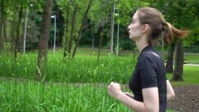 De jonge atletische looppas van de vrouwensprinter in park bij zomer Langzame motie stock videobeelden