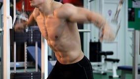 De jonge atletische mens voert spieroefeningen uit stock videobeelden