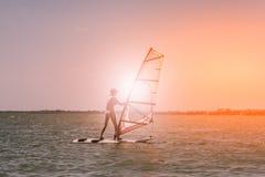 De jonge atletische slanke meisjeszeilen op een windsurf schepen in de open zee op de zomervakantie in bij toevlucht windsurfing stock afbeelding