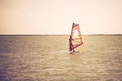 De jonge atletische slanke meisjeszeilen op een windsurf schepen in de open zee op de zomervakantie in bij toevlucht windsurfing royalty-vrije stock foto's