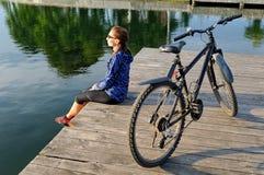 De jonge atletische vrouw in sportkleding zit naast een fiets Stock Foto
