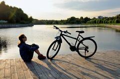 De jonge atletische vrouw in sportkleding zit naast een fiets Stock Fotografie