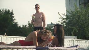 De jonge attrective mens spreekt met twee schuwe en glimlachende meisjes, die coctails op het zitkamer dichtbij zwembad drinken stock videobeelden