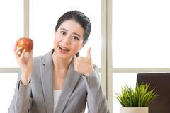 De jonge Aziatische appel en de duim van de onderneemsterholding omhoog Stock Fotografie