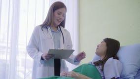 De jonge Aziatische artsenvrouw toont informatiebehandeling op klembord voor vrouwenpatiënt in ziek bed stock videobeelden