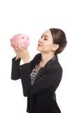 De jonge Aziatische bedrijfsvrouw kust een roze muntstukbank Royalty-vrije Stock Afbeeldingen