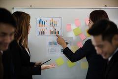 De jonge Aziatische bedrijfsvrouw maakte een presentatie beschrijvend gr. stock foto's