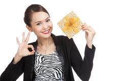 De jonge Aziatische bedrijfsvrouw toont o.k. met een gouden giftdoos Stock Foto's