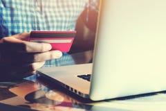 De jonge Aziatische creditcard van de mensenholding met het gebruiken van laptop en online Stock Foto