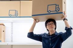 De jonge Aziatische gelukkige mens het dragen overheadkosten van de kartondoos royalty-vrije stock fotografie