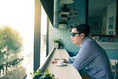 De jonge Aziatische gelukkige mens kijkt door duidelijk venster en het denken dur royalty-vrije stock foto's