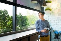De jonge Aziatische glazen die van het de greepoog van de mensenhand uit venster, Cas kijken stock fotografie
